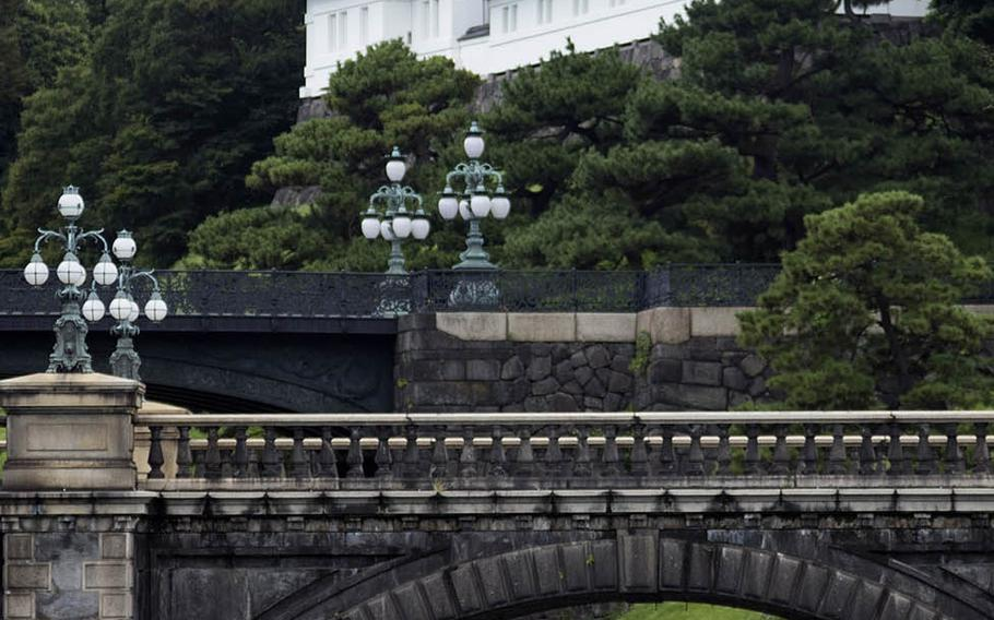 Travelers stand outside the Imperial Palace grounds in central Tokyo, Sept. 3, 2020.
