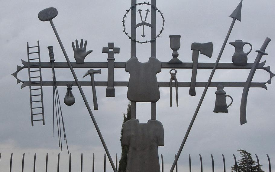 This eclectic metal sculpture includes work tools from a variety of professions outside the San Lorenzo Roman Catholic Church in Marsure, Italy.
