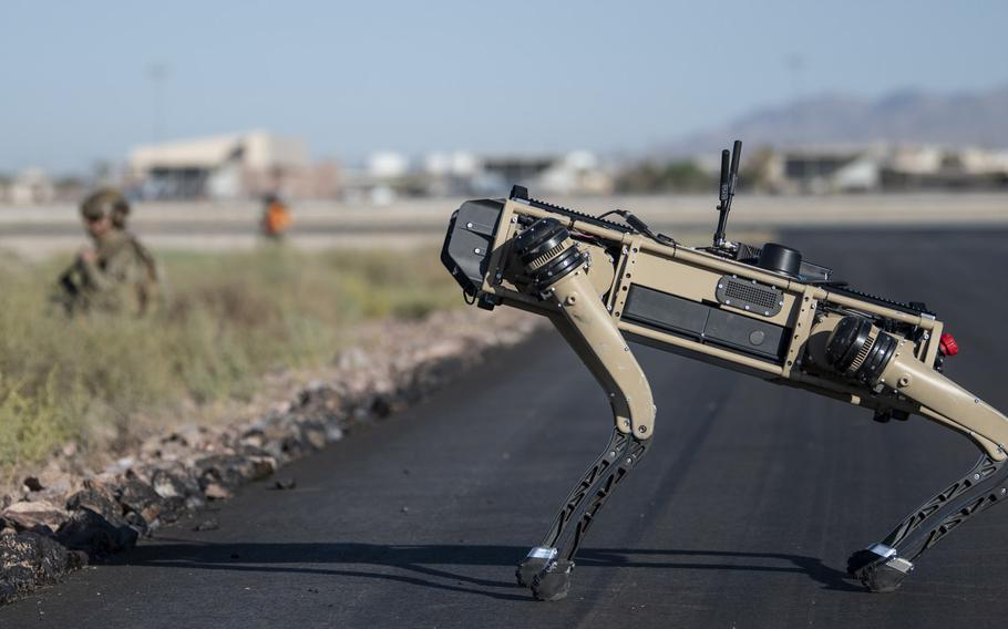 Tech. Sgt. John Rodriguez, 321st Contingency Response Squadron security team, patrols with a Ghost Robotics Vision 60 prototype during an exercise on Nellis Air Force Base, Nev., Sept. 3, 2020. Air Force scientists are exploring how humans will interact with artificial intelligence systems when they behave independently.