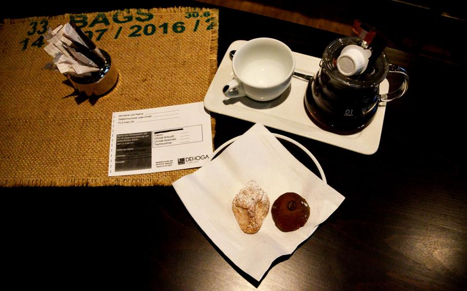 A pot of Peru Tunki drip coffee served with individual pots of cream and a small cookie, almond and mocha Italian pastries, a pot of sugar and a paper to fill in with contact tracing information for the coronavirus sit on a table at Cafe Plaisir in Saarlouis, Germany, on Oct. 17, 2020.
