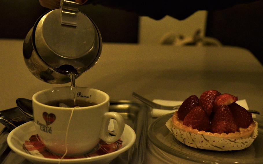 A strawberry tart and a pot of fruit tea at Patisserie Antoine in Bitche, France, on Oct. 10, 2020. The tart consisted of a pastry bed topped with confectioner's custard and crowned with fresh strawberries.