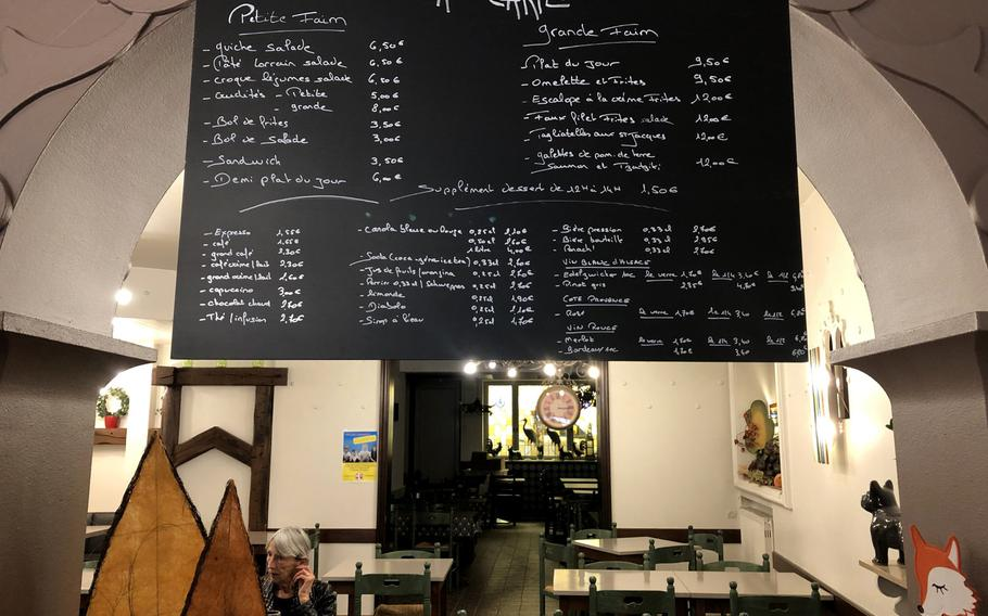 A woman sits near the menu in Patisserie Antoine in Bitche, France, on Oct. 10, 2020. In addition to small and large dishes such as quiche with salade and tagliatelle with scallops, the cafe offers an array of pastries and beverages, including tea and coffee.