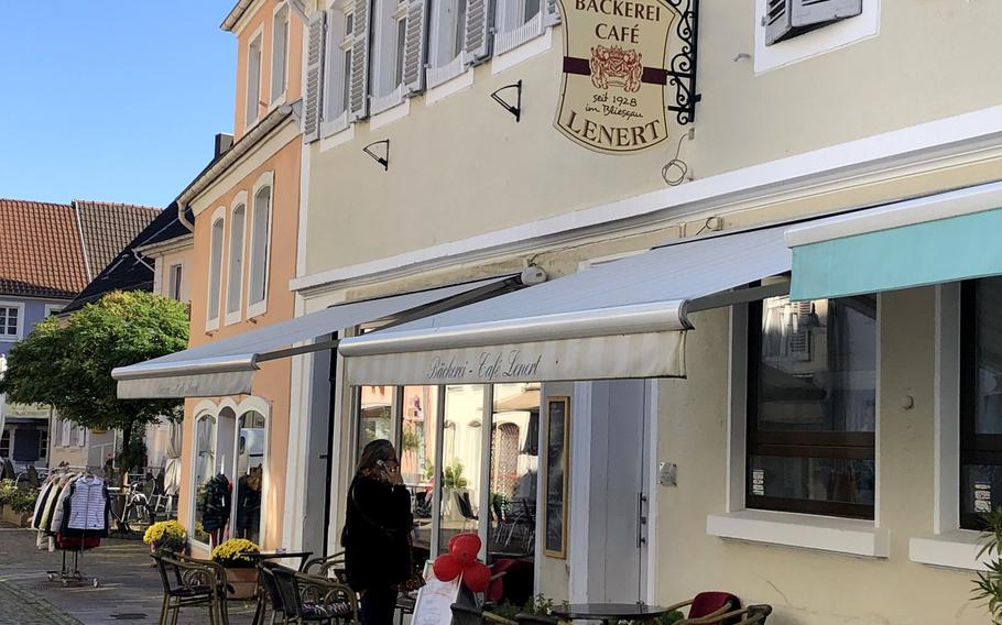 A woman finishes a phone conversation before entering Cafe Lenert in Blieskastel, Germany, on Oct. 10, 2020. The cafe is open seven days a week, and offers all-day breakfast, baked goods, and sandwiches.