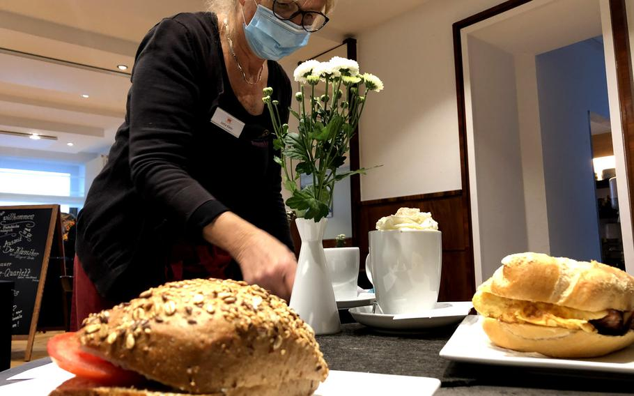 """Server Jutta Klein delivers a Weisser Hoefling sandwich (left), an Ei Love You (right), described by the customer as """"a fancy Egg McMuffin,"""" a hot chocolate with a dollop of whipped cream and a coffee at Cafe Lenert in Blieskastel, Germany, on Oct. 10, 2020."""