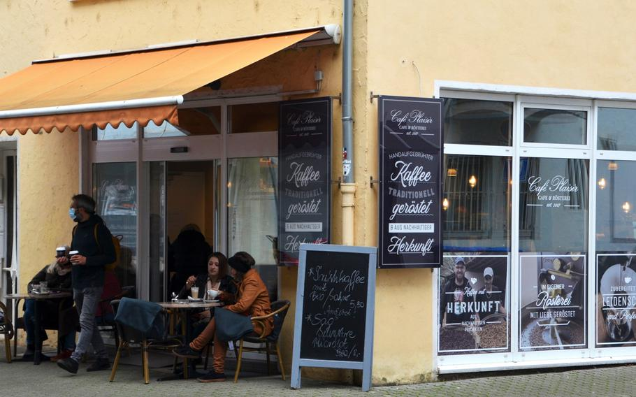 A customer wearing a face mask leaves Cafe Plaisir in Saarlouis, Germany, with two beverages, while other customers enjoy their beverages outside and inside the cafe, on the edge of the city's pedestrian zone.