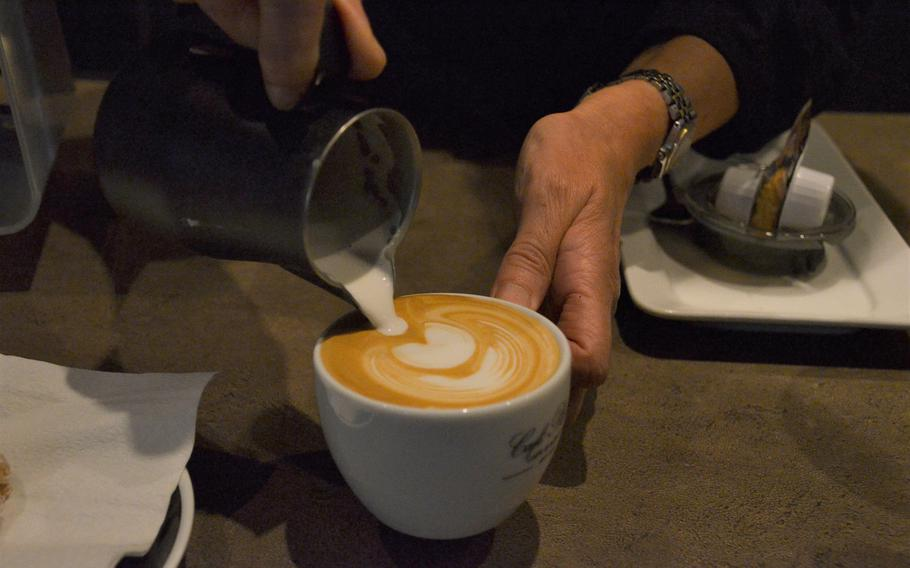 A barista at Cafe Plaisir in Saarlouis, Germany, pours steamed milk onto espresso coffee to make a cappuccino on Oct. 17, 2020. Cafe Plaisir sources coffee beans from farms around the world and roasts its own coffee.