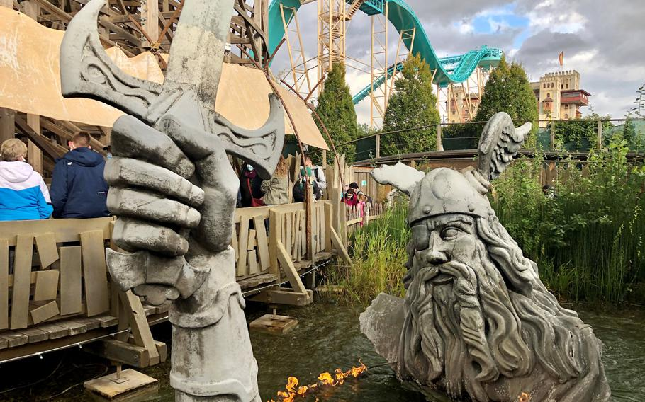 A large Norse god statue emerges from the water next to the Wodan Timbercoaster in Iceland Village at Europa Park.