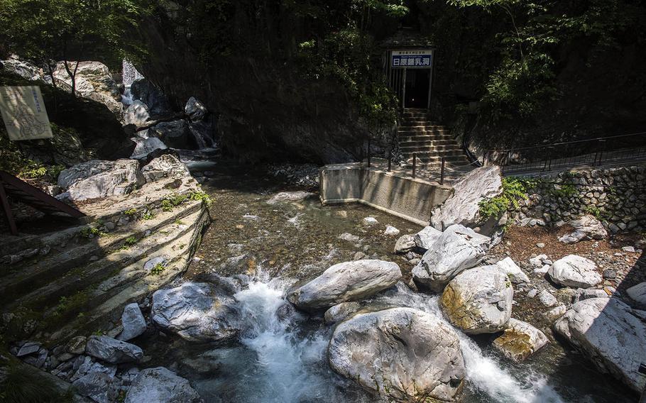 Walk across the Nippara River to enter the Nippara Limestone Cave near Okutama, Japan.