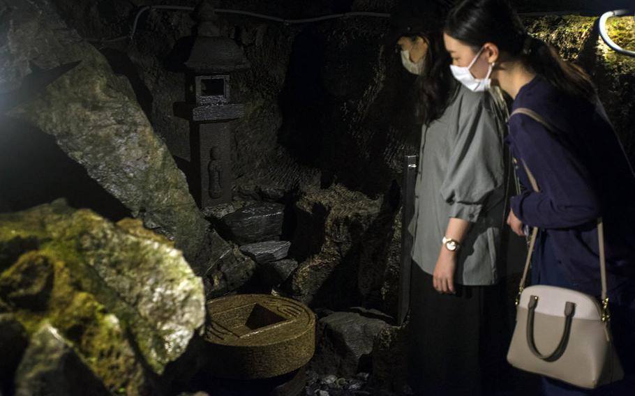 Visitors to the Nippara Limestone Cave near Okutama, Japan, check out a worship spot used by monks from the Shugendo sect of Buddhism.