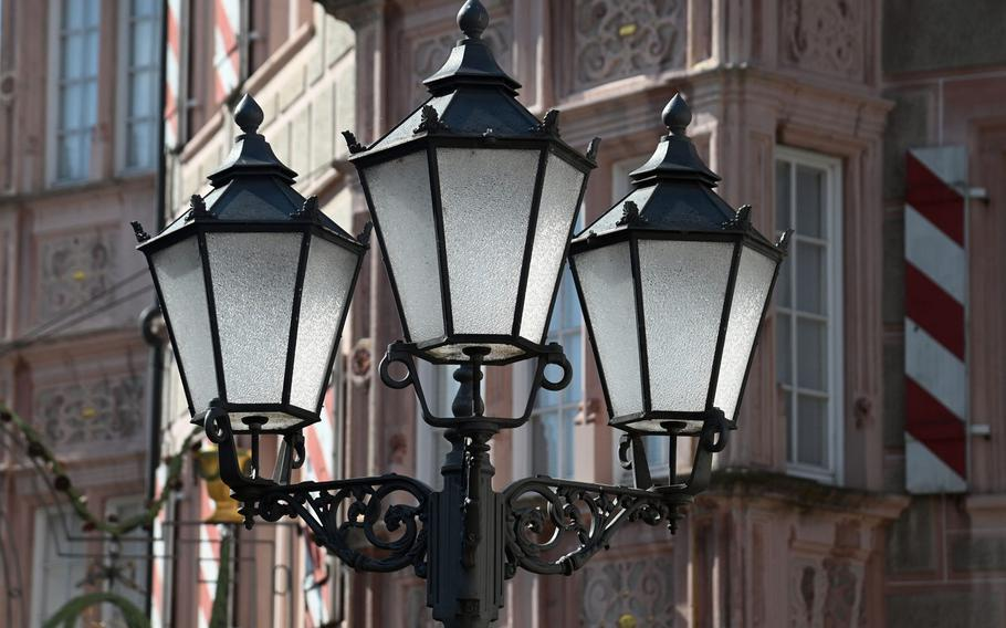 A trio of old-fashioned streetlights stand in front of the Gasthaus zum Engel, a Renaissance building in Bad Bergzabern, Germany.