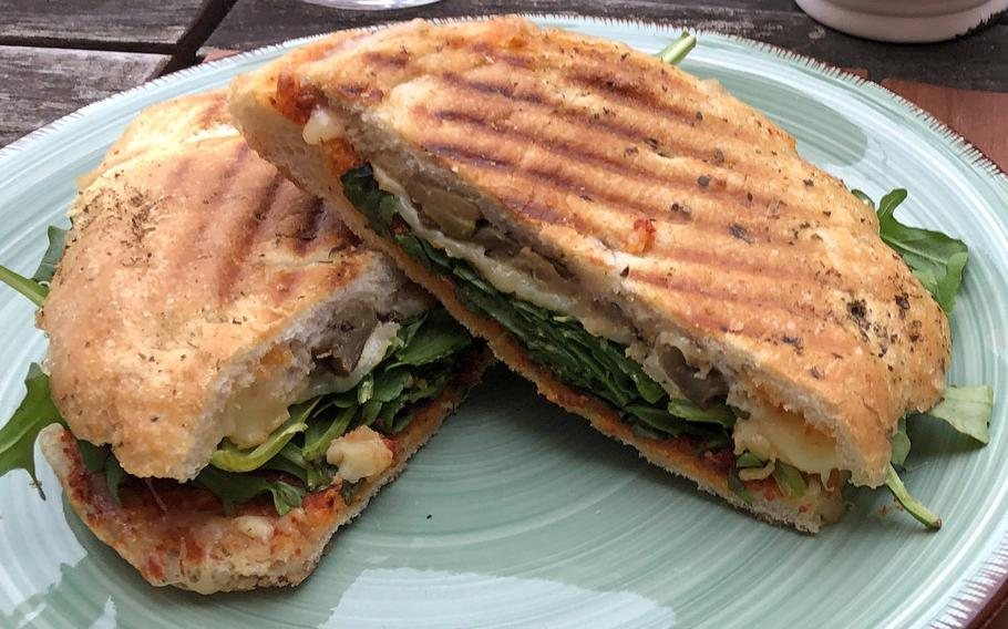 A takeout focaccia Sicilia from Vinocentral in Darmstadt, Germany. It includes olive tapenade, grilled, marinated vegetables and Provolone cheese on a bed of arugula.