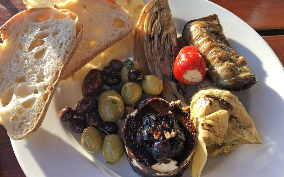 An antipasti plate at Vinocentral in Darmstadt, Germany. This one includes olives, fennel, grilled, marinated eggplant, an artichoke heart and goat cheese topped with balsamic cream and cranberries.