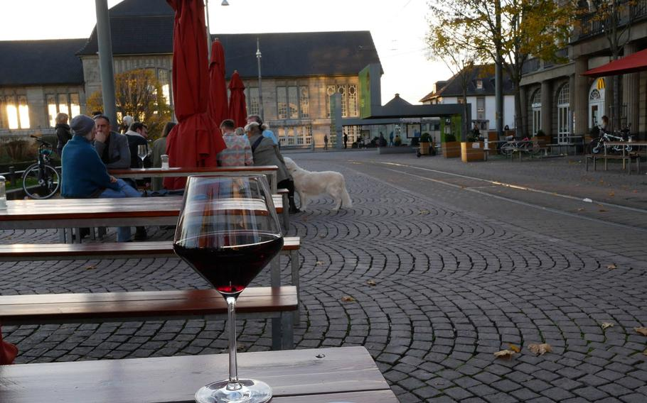A glass of primitivo from the Puglia region of Italy at the Vinocentral in Darmstadt, Germany. In the background is the city's main train station.