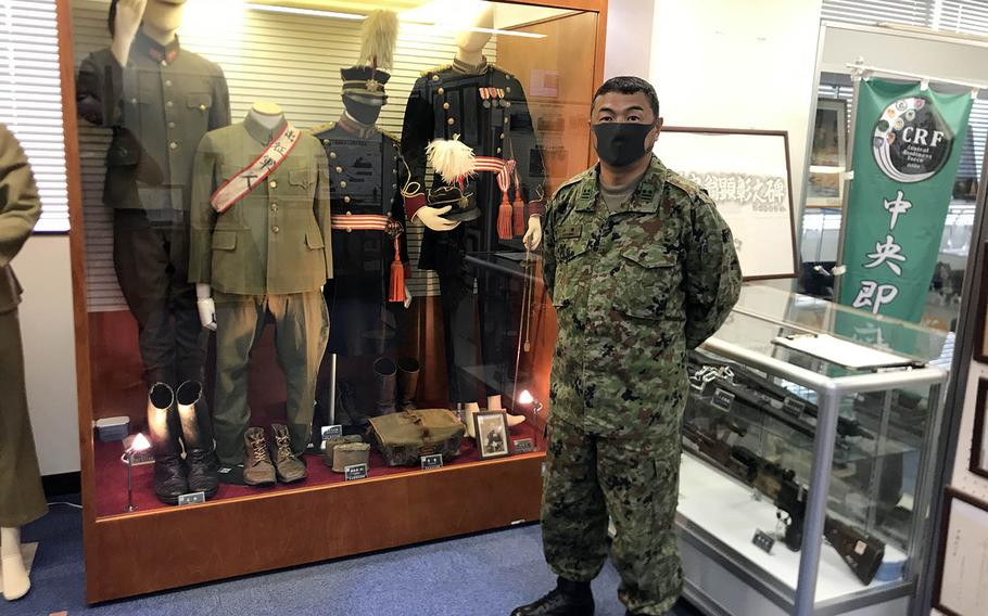 Lt. Col. Akira Ozawa of the Japan Ground Self-Defense Force poses with old Japanese Imperial Army uniforms and weapons inside a small museum at Camp Zama, Japan.