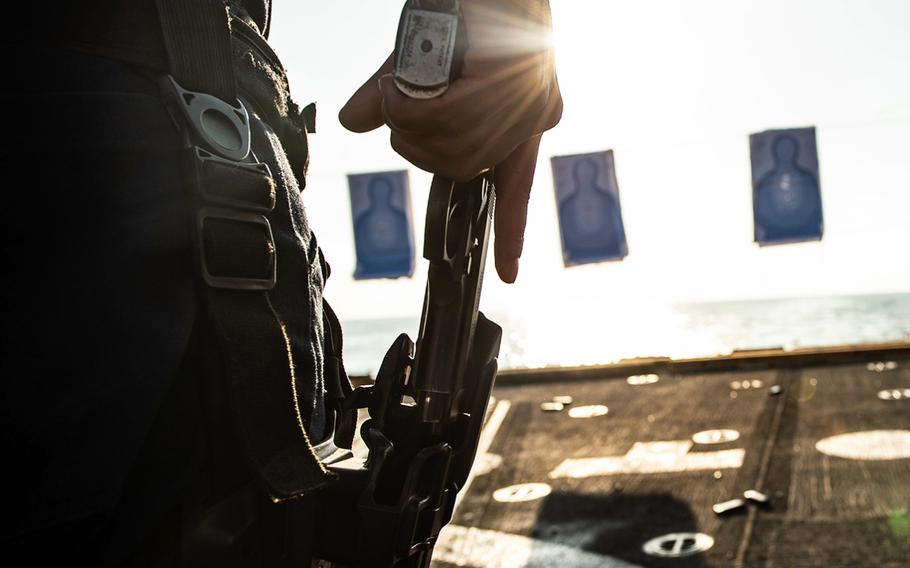 A sailor draws an M9 service pistol from his holster during a gun shoot on the flight deck of the guided-missile destroyer USS Farragut in the Gulf of Oman on Dec. 13, 2019.