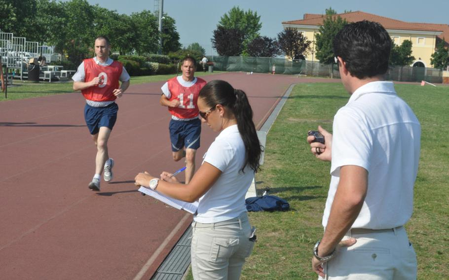 Eleonora Paronuzzi and Luca Rustja keep tabs on Tech. Sgt. Jeremy Tucker, left, and Airman 1st Class Brandon Detter as they run around the track at Aviano Air Base in Italy during the first day of the Air Force's new fitness test.