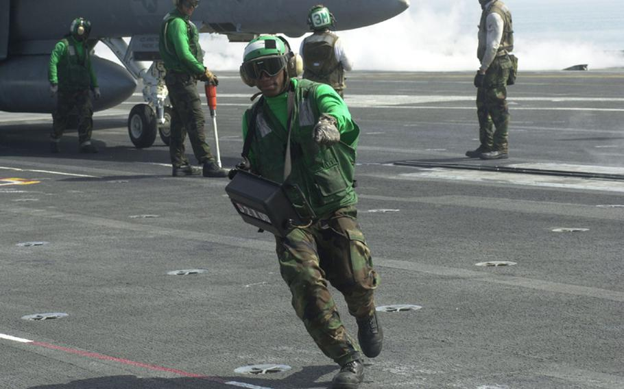 A member of the crew of the USS George Washington signals to his counterparts as an aircraft prepares to take off during the Invincible Spirit exercise on Sunday in the Sea of Japan.