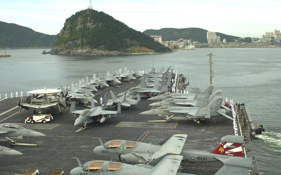 The USS George Washington pulls away from Pusan in South Korea on its way Sunday to participate in the Invincible Spirit joint military exercise being staged for four days by the U.S. and South Korea.