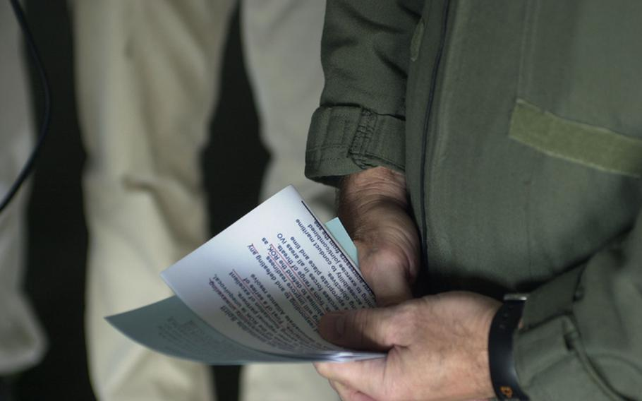 Capt. Ross Myers, commander of USS George Washington Carrier Air Wing 5, clutches pieces of paper with 'talking points' as he is interviewed by the media Sunday during the Invincible Spirit military exercise.