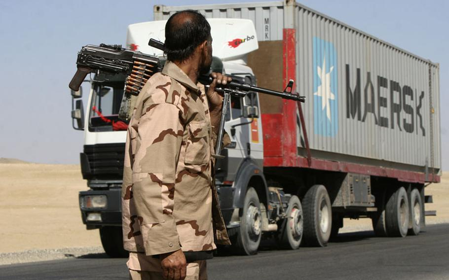 A private security contractor watches a NATO supply truck drive past in Ghazni province,  southwest of Kabul in October.