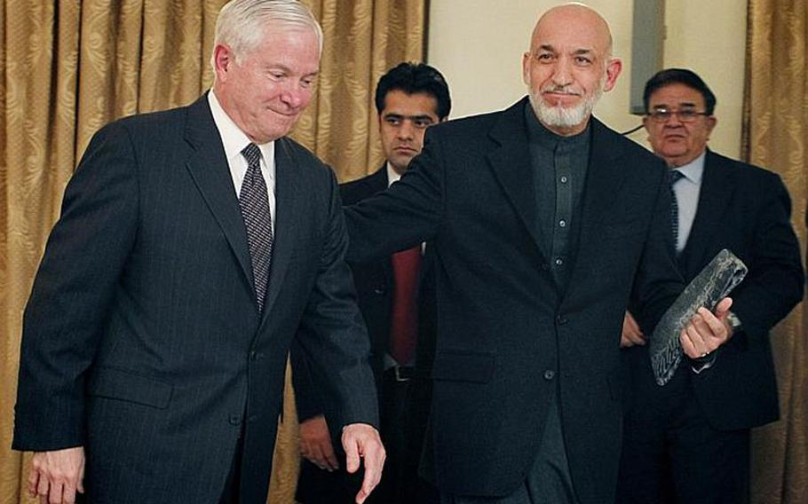 In this file photo, Defense Secretary Robert Gates is escorted by Afghan President Hamid Karzai after a joint press conference at the presidential palace in Kabul during a past visit.
