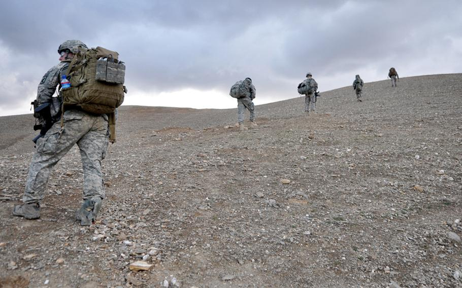 Soldiers with the 173rd Airborne Brigade Combat Team's Company C, 1st Battalion, 503rd Infantry Regiment patrol above the Tangi Valley in Wardak province, Afghanistan. Top right: Staff Sgt. Terek Khalil, a medic from the 503rd's 2nd Battalion, treats and bandages an arm injury on a child in Chiriac Valley, Afghanistan, on Oct. 24. Bottom right: A medic with the 503rd's 1st Battalion treats an Afghan flood victim near Combat Outpost Nerkh in Wardak province Aug. 11.