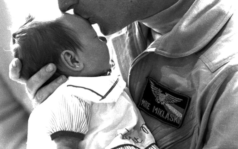 Lt. j.g. Mike Miklaski meets his five-week-old daughter, Jessica, for the first time as he and other pilots from the USS Midway's carrier air wing return home from the Gulf War in April, 1991.