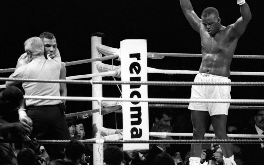 """James """"Buster"""" Douglas celebrates his win as Mike Tyson is supported by referee Octavio Meyran."""