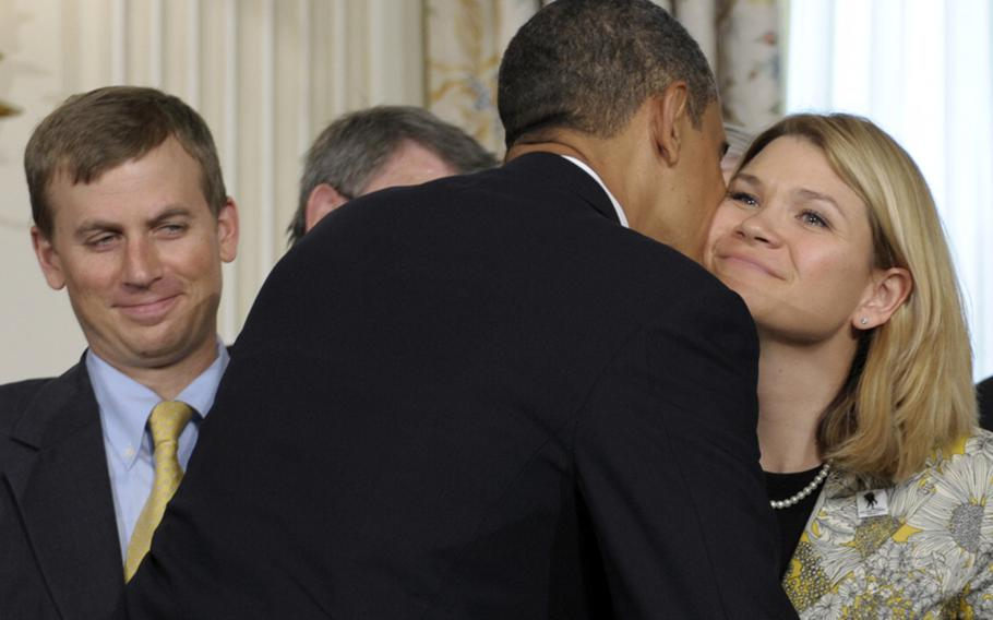 In 2010 file photo, President Obama gives Sarah Wade, wife of Army Sgt. Ted Wade, left, a kiss on the cheek before he signed the Caregivers and Veterans Omnibus Health Services Act..