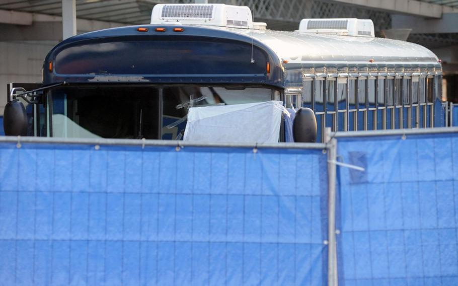 A fence surrounds the military bus where a gunman shot and killed two U.S. airmen and wounded  two others at Frankfurt's international airport in this March photo.