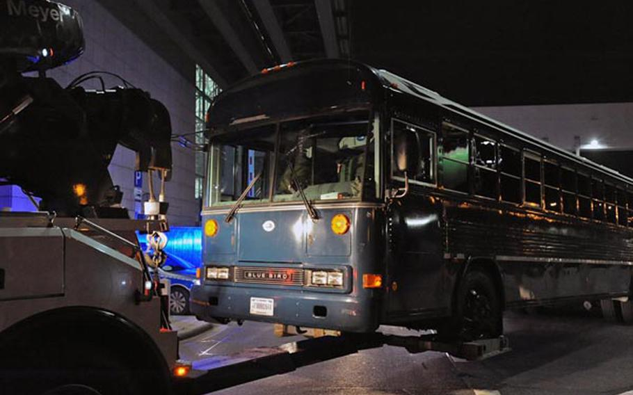 A U.S. Air Force bus is towed from in front of Frankfurt International Airport's Terminal 2. On Wednesday afternoon a gunman shot four Americas, killing two. According to German police, the bus was to be towed to a hall on airport grounds for further investigation.