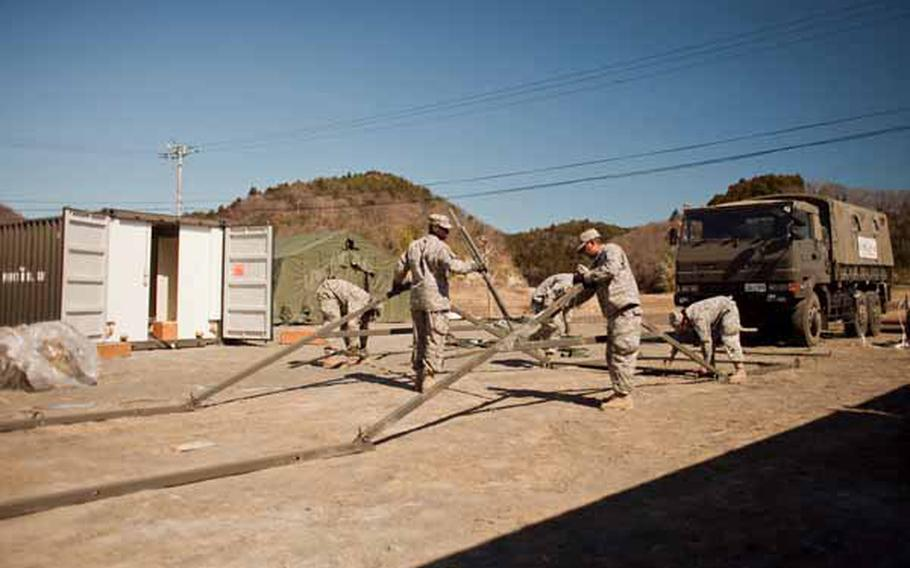 Soldiers from Logistics Task Force 35 work to construct a second shower unit near the Ono Civic Center in Higashi Matsushima, Japan. The units contain 12 showers and six sinks.