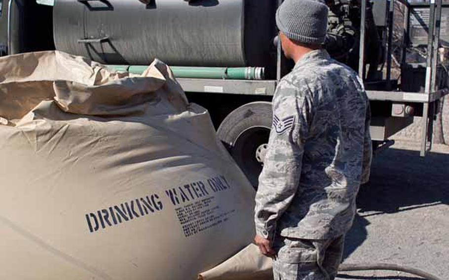 Airman 1st Class Cody Hoover (seated) and Staff Sgt. Alvin Pablo, from the 374th Civil Engineering Squadron on Yokota Air Base, fill a flexible water container with about 2,000 gallons of water, which will be used for shower stations set up by soldiers from Logistics Task Force 35 for displaced residents living at the Ono Civic Center shelter in Higashimatsushima, Japan. Pablo said they transport about 20,000 gallons of water to the site each day.