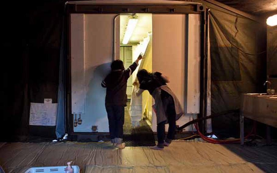 Kiroko Abe, 42, (left) and Yukari Kaimura, 39, displaced residents living at the Ono Civic Center shelter in Higashimatsushima, Japan, look at the shower facilities set up by soldiers from Logistics Task Force 35. The Army constructed two shower tents holding 24 showers and 12 sinks total.
