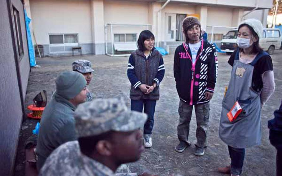 Displaced residents from the Ono Civic Center shelter in Higashimatsushima, Japan, talk with soldiers from Logistics Task Force 35, who spent the afternoon constructing two shower units for the residents.