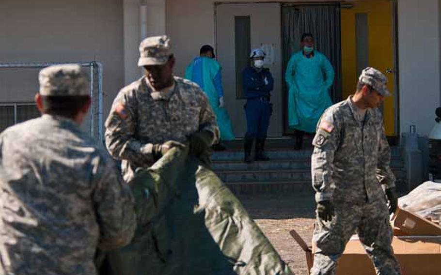 Morgue workers look on as soldiers from Logistics Task Force 35 work to construct a shower tent near the Ono Civic Center in Higashimatsushima, Japan.