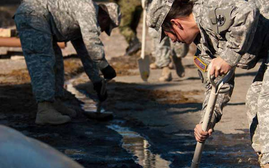 Soldiers from Logistics Task Force 35, along with Japan Self-Defense Force troops, work to dig a trench for run-off water from the shower units they set up near the Ono Civic Center in Higashimatsushima, Japan.