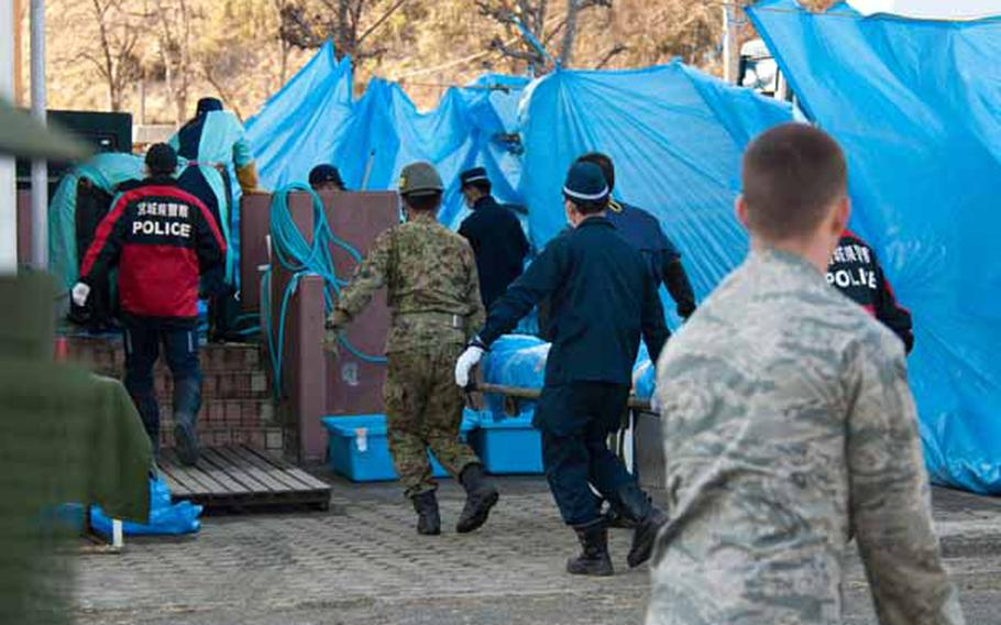 An airman looks on as morgue workers, police officers and Japan Self-Defense Force troops bring a body to a morge. Soldiers from Logistics Task Force 35, along with a few airmen from the 374th Civil Engineering Squadron from Yokota Air Base, established two shower stations near the Ono Civic Center shelter in Higashimatsushima, Japan, which also borders a morgue.