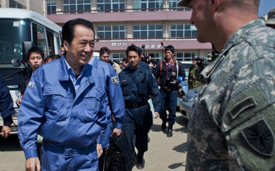 Japan Prime Minister Naoto Kan approaches Army Col. Lance Koenig, commander of Joint Logistics Task Force 10, during his visit to Ishinomaki Commercial High School shelter in Ishinomaki, Japan. Soldiers and Marines from the task force have been working to clean up the school grounds and were thanked by Kan for their efforts.
