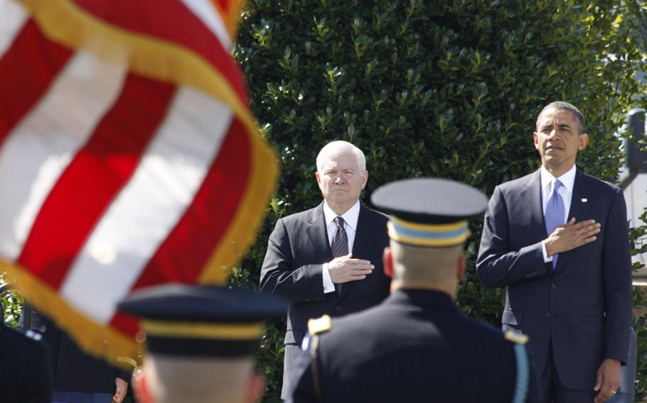 President Barack Obama and outgoing Defense Secretary Robert Gates salute during a ceremony June 30, 2011, honoring Gates' time at the Pentagon.