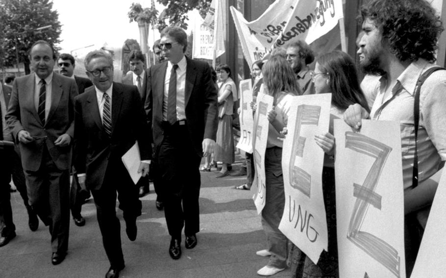 """Former Secretary of State Henry Kissinger walks past a line of protesters on his way to speak at a German-American tricentennial ceremony at Worms, Germany, in 1983. At left is German Foreign Minister Hans-Dietrich Genscher. The protesters are holding letters forming the word """"freeze,"""" in connection with nuclear disarmament."""