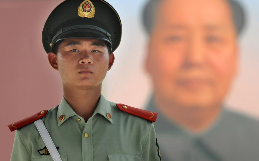 A young Chinese soldier stands at his post under the watchful gaze of Mao Tse Tung at Beijing's Tiananmen Square, August 3, 2008.