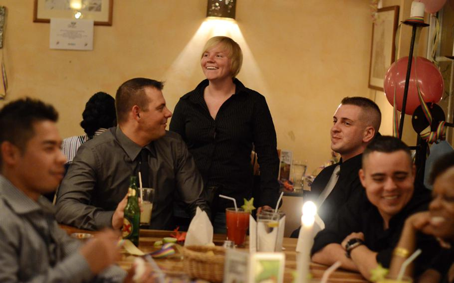 """U.S. Air Force Staff Sgt. Ashley Carothers, a  leader of OutServe Germany, laughs with Master Sgt. Kristopher Kobernus (left), guest speaker, and Staff Sgt. John Tegeler, leader of OutServe Germany, during their celebration of repeal of """"don't ask don't tell."""""""