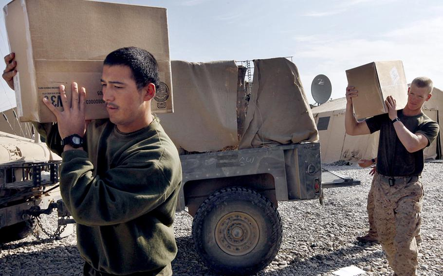 Navy Hospitalman Michael Nakamura, left, and Marine Lance Corp. Tyler Turlington, of Jacksonville, North Carolina, carry boxes of supplies to the mess area of the remote FOB Hassanabad, Afghanistan, during a re-supply session in 2009.