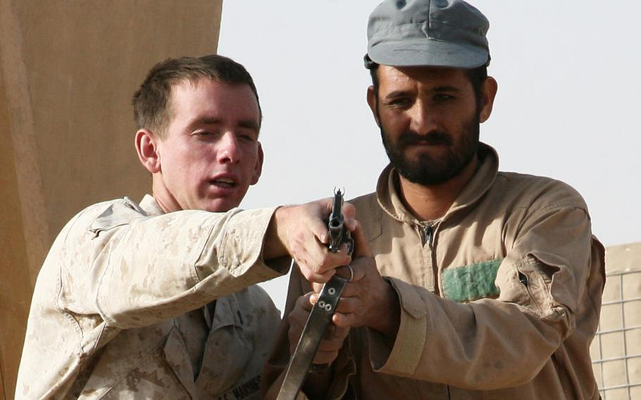 Cpl. Tyler M. Rousselle, a Joint Security Academy Southwest instructor, explains proper weapons handling to an Afghan National Police recruit during a field exercise at Camp Leatherneck, Afghanistan, in August 2010. Beginning in 2012, the U.S. will shift its mission in the country to focus on training and advising Afghan forces.