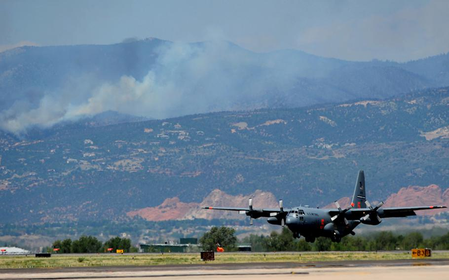 A C-130 Hercules lands at Peterson Air Force Base in Colorado Springs, Colo., for more fire retardant Tuesday, June 26, 2012, while fighting the Waldo Canyon Fire in the background. Four air tankers were battling the fire west of Colorado Springs, Colo. The tankers drop 3,000 gallons of water or fire retardant in less than five seconds, covering an area one-quarter mile long by 100 feet wide.