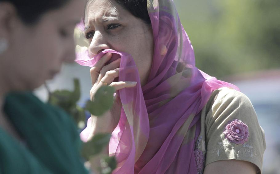 A woman looks on near the scene of a shooting at the Sikh Temple in Oak Creek, Wisconsin on Aug. 5, 2012.