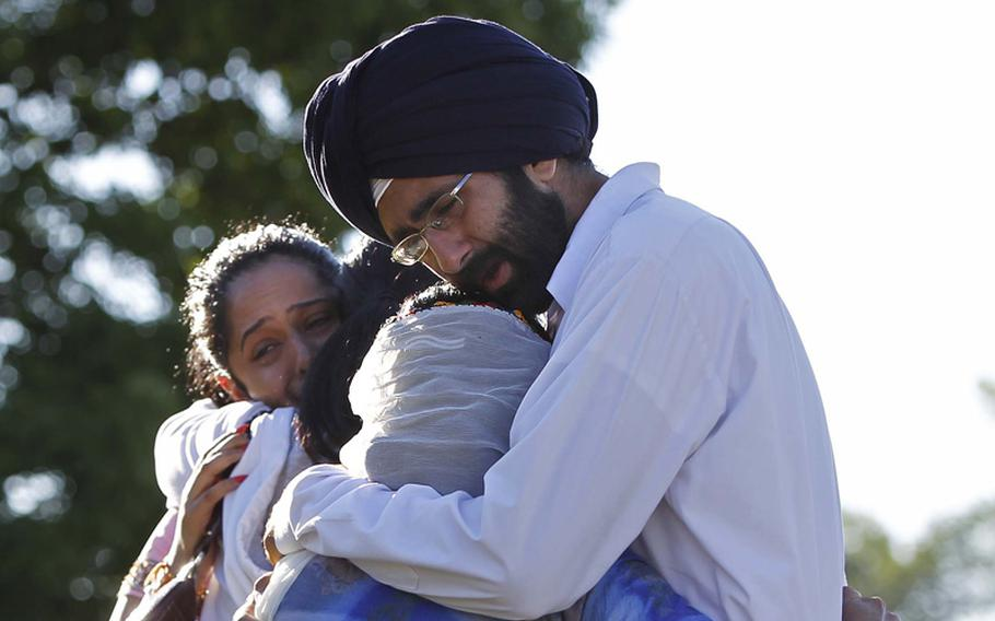 Kanwardeep Singh Kaleka, right, hugs an unidentified woman while his sister Simran Kaleka, left, hugs another unidentified relative, Monday, August 6, 2012, as they meet and mourn the loss of their uncle Satwant Singh Kaleka, president of the Sikh temple, who died in Sunday's temple shootings in Oak Creek, Wisconsin.