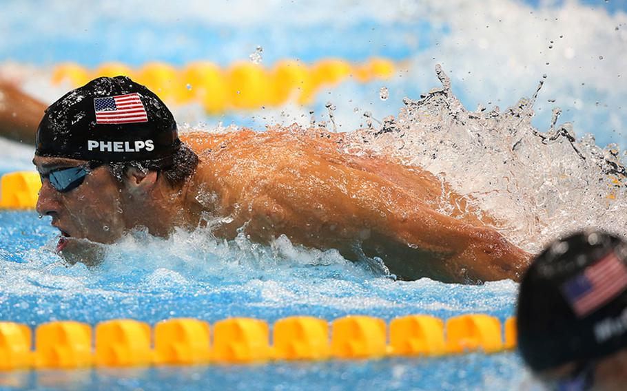Michael Phelps of the United States on his way to winning the men's 100 meter butterfly at the 2012 Summer Games in London, England, on Aug. 3, 2012. Viewers are complaining about AFN's broadcast schedule of the Olympic games, which has forced some to wait until after midnight to catch the feats of Olympians such as Phelps and Usain Bolt.