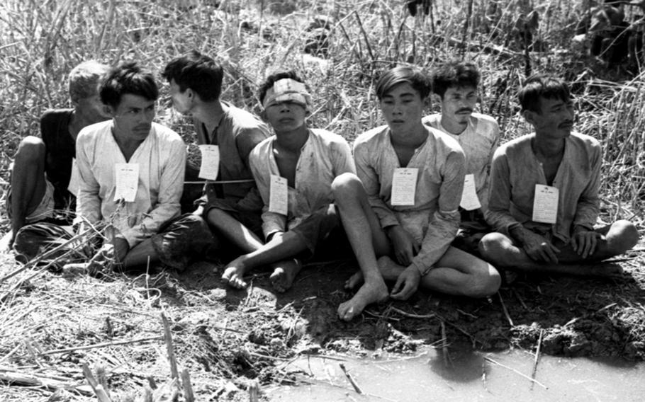 Viet Cong detainees, bound together, await transportation to an interrogation center.